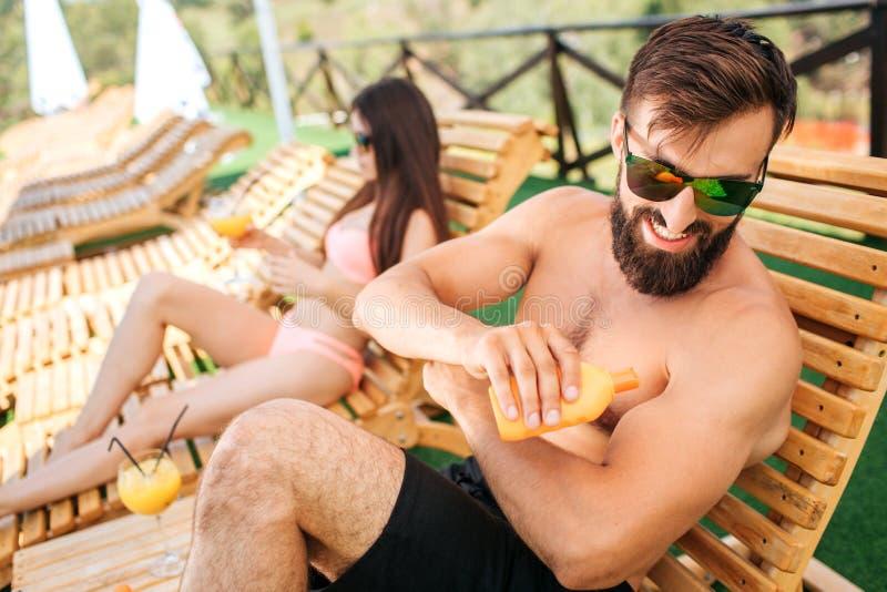 Une photo de type barbu se reposant sur le lit pliant et mise de la crème de sunproof sur la peau de la bouteille orange Il utili photo stock