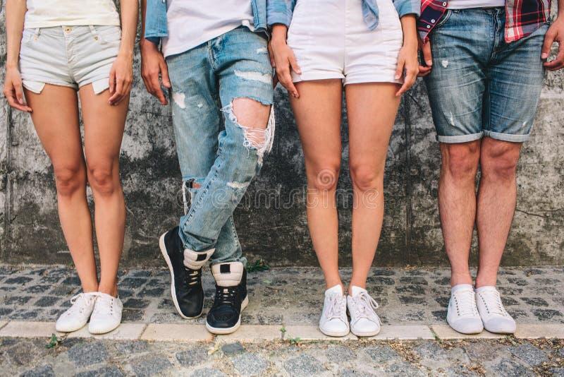 Une photo des jambes de ` d'ados Trois d'entre eux se tiennent droits tandis que l'homme dans des jeans tient la jambe gauche au- image stock
