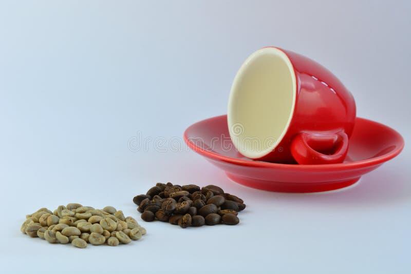 Une photo en gros plan d'une tasse de café rouge lumineuse d'expresso, de quelques grains de café verts et de quelques grains de  photographie stock libre de droits