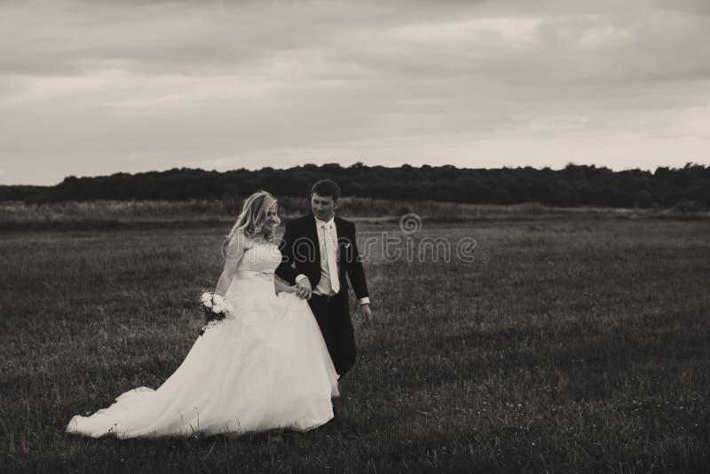Une photo noire et blanche d'un couple de mariage marchant sur le fie photo libre de droits