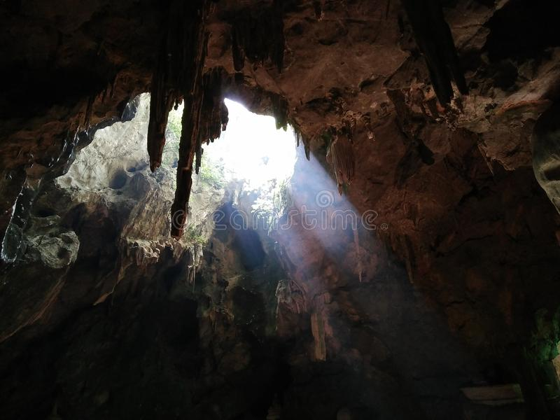 Une photo prise de l'intérieur d'une caverne avec des axes de lumière de midi photos libres de droits