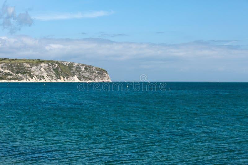 Une photo prise une journée de printemps à la plage de Swanage regardant vers les bateaux sur la mer et la côte jurasic rayent image libre de droits