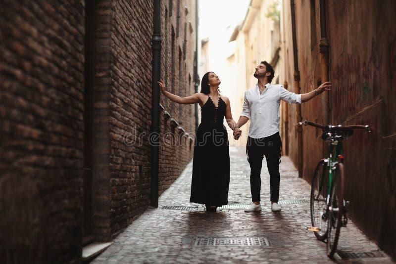 Une photo sensuelle des deux jeunes dans une rue étroite de la vieille ville Promenade avec un v?lo images libres de droits