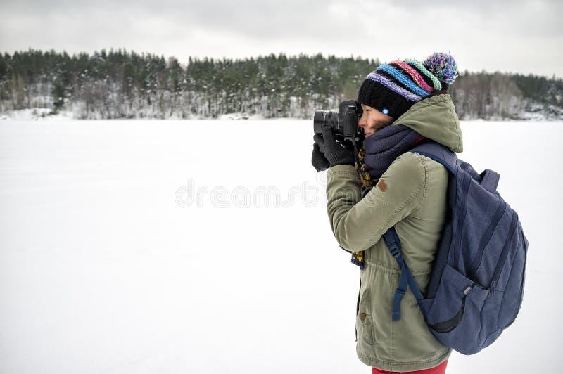 Une photographe de femme dans des vêtements chauds et un sac à dos tient une caméra dans des ses mains et prend des photos d'un p photo libre de droits