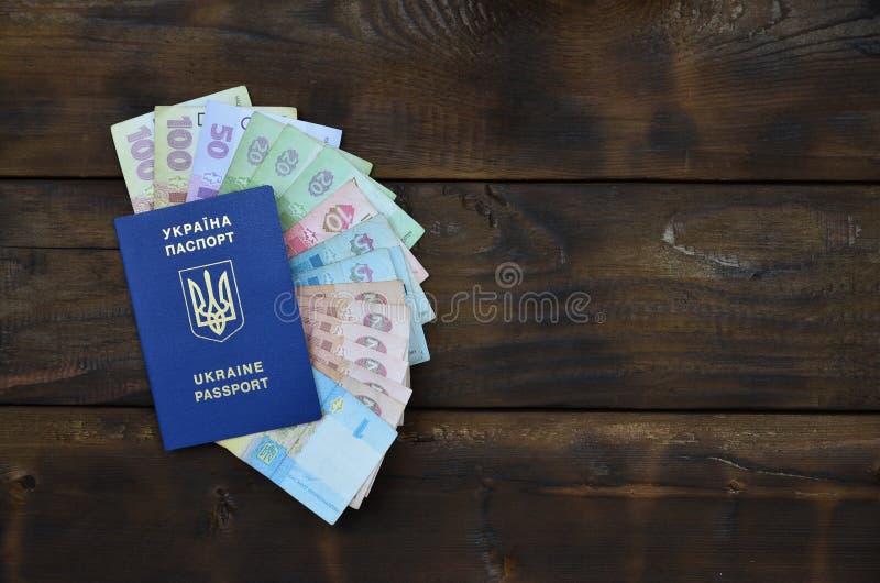 Une photographie d'un passeport ukrainien et un argent ukrainien sur une surface en bois Le concept de gagner l'argent pour photos stock