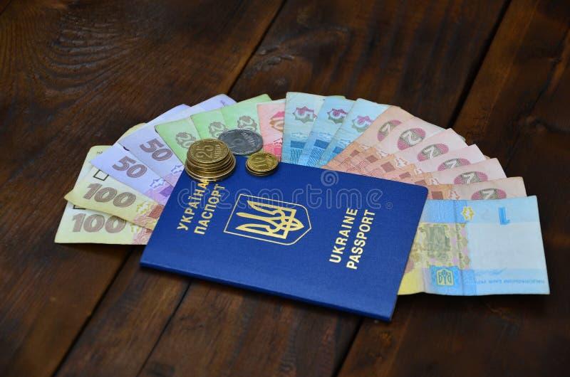 Une photographie d'un passeport ukrainien et un argent ukrainien sur une surface en bois Le concept de gagner l'argent pour image libre de droits