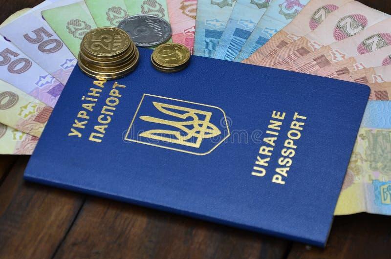 Une photographie d'un passeport ukrainien et un argent ukrainien sur une surface en bois Le concept de gagner l'argent pour photographie stock