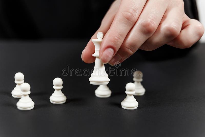 Une pièce d'échecs en mouvement de roi de main humaine à la table image stock
