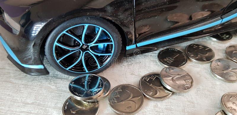 Une pièce de monnaie israélienne de shekel près de jouet en métal de noir de Bugatti Chiron avec la réflexion d'argent de la roue images stock