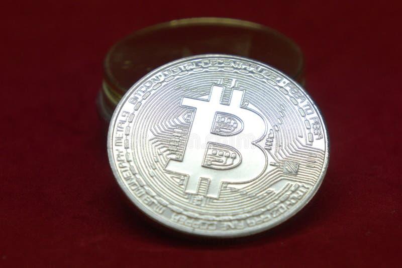 Une pile d'or et de pièces de monnaie argentées de cryptocurrency avec le bitcoin dans l'avant sur un fond rouge de velours image stock