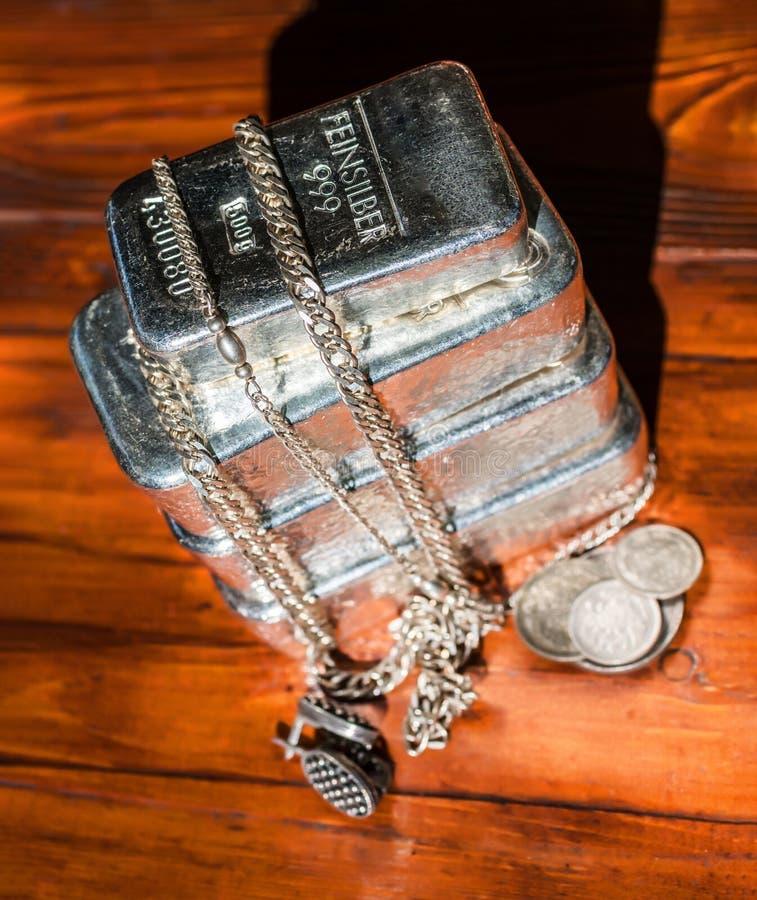 Une pile de barres argentées de fonte de poids différent, de diverses pièces en argent et de bijoux sur un fond d'acajou photos libres de droits