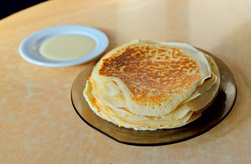 Une pile de crêpes vermeilles d'un plat transparent et une soucoupe blanche avec du lait condensé sont sur la table photographie stock