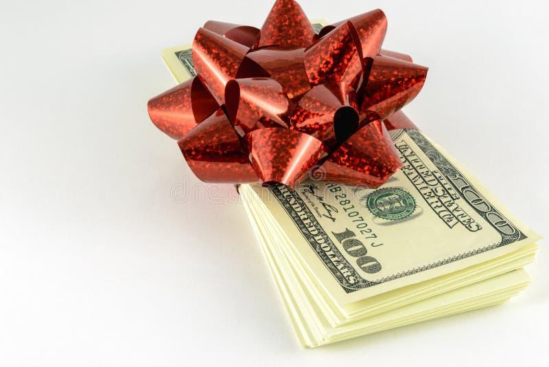 Une pile de dollars et un cadeau rouge cintrent image stock