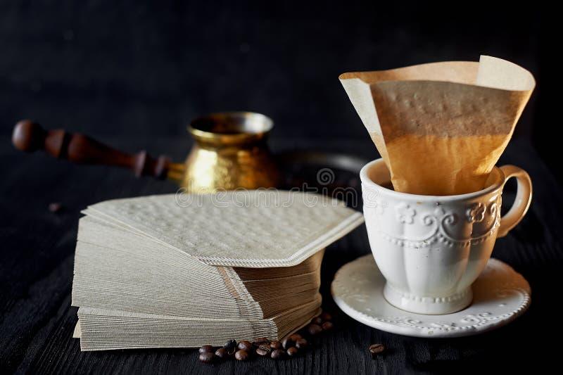 Une pile de filtres de café de papier d'emballage, et tasse blanche Macro photographie stock