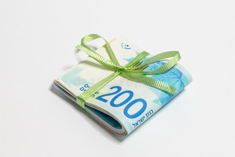Une pile de nouveaux billets de banque israéliens pliés de valeur différente dans les shekels NIS attachés avec le ruban vert sur photographie stock