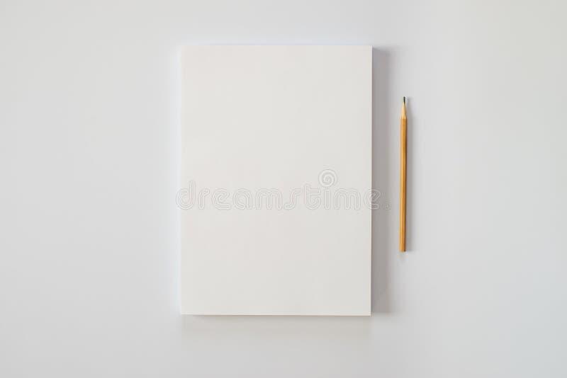 Une pile de pages blanches de papier et d'un crayon sur un fond blanc photos libres de droits