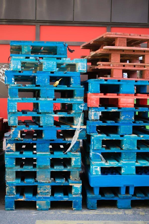 Une pile de palettes en bois bleues et rouges image libre de droits
