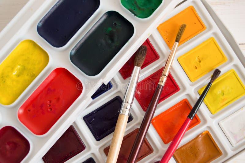 Une pile de peinture d'aquarelle avec trois brosses photographie stock