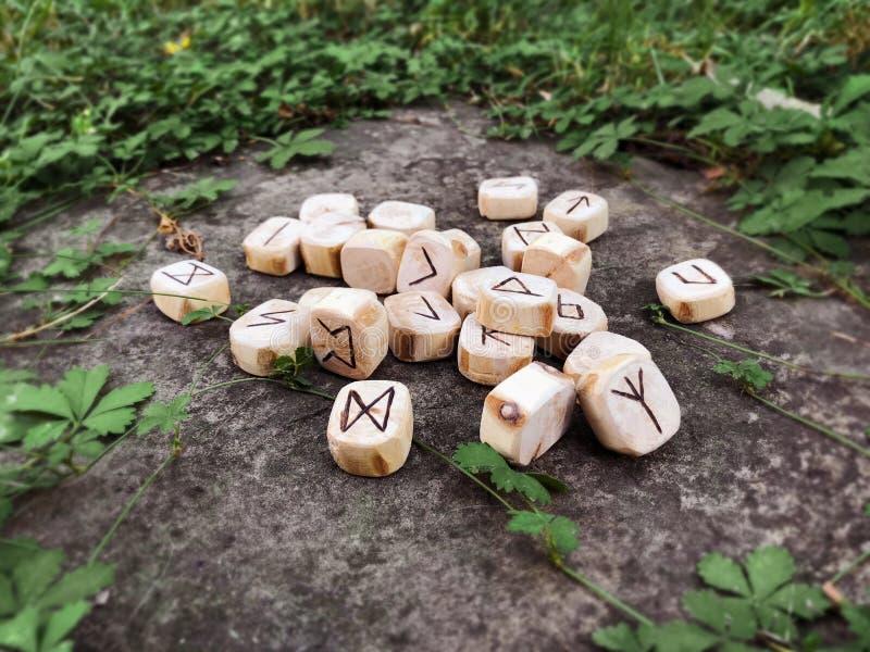 Une pile de runes en bois aux runes en bois de forêt se trouvent sur un fond de roche dans l'herbe verte Des runes sont coupées d images stock