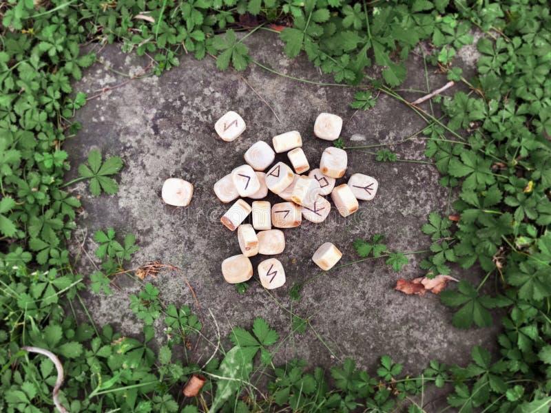 Une pile de runes en bois aux runes en bois de forêt se trouvent sur un fond de roche dans l'herbe verte Des runes sont coupées d photographie stock