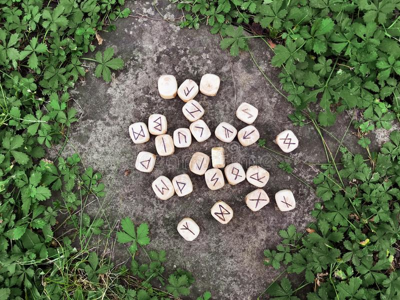 Une pile de runes en bois aux runes en bois de forêt se trouvent sur un fond de roche dans l'herbe verte Des runes sont coupées d image libre de droits