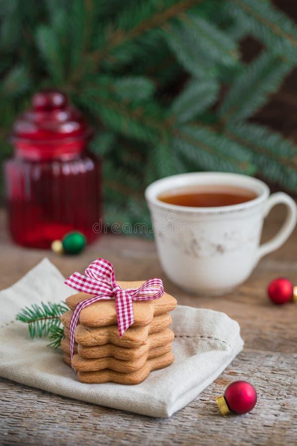 Une pile de serviette d'onbeige de biscuits de Noël de pain d'épice avec une tasse de thé photographie stock