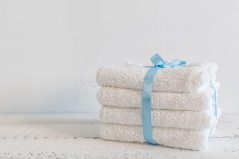 Une pile de serviettes de bain blanches avec la bande bleue sur la table en bois blanche Station thermale et bien-être, textile d photographie stock