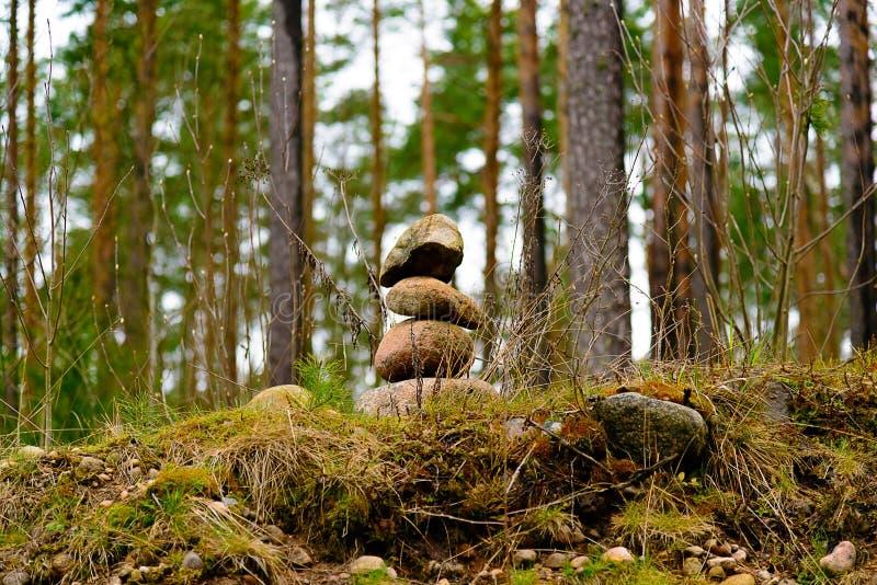 Une pile de trois pierres dans la forêt parmi les arbres photos stock
