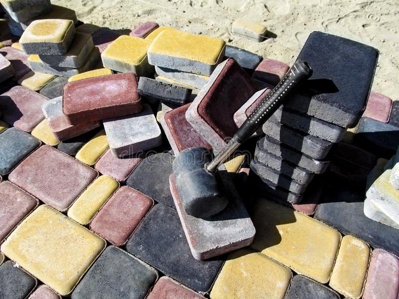Une pile des briques colorées ` de ville de ` de tuiles du vieux et d'un marteau en caoutchouc pour étendre les pavés photos libres de droits