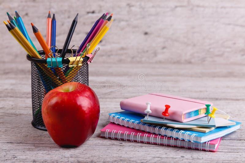 Une pile des carnets, des crayons colorés dans un récipient et d'une pomme Sur une surface en bois photos stock