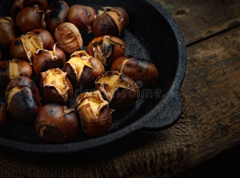 Une pile des châtaignes comestibles a rôti dans une casserole de fonte sur une surface en bois foncée avec un tissu de textile images libres de droits