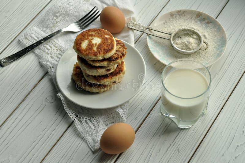 Une pile des crêpes frites de fromage, une fourchette sur une serviette de toile blanche, un verre de lait, oeufs secveral et un  images stock