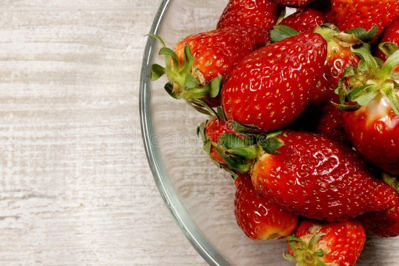 Une pile des fraises fraîches rouges dans un bol en verre photographie stock libre de droits