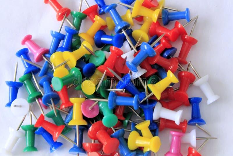 Une pile des goupilles colorées de poussée sur un fond blanc photographie stock libre de droits