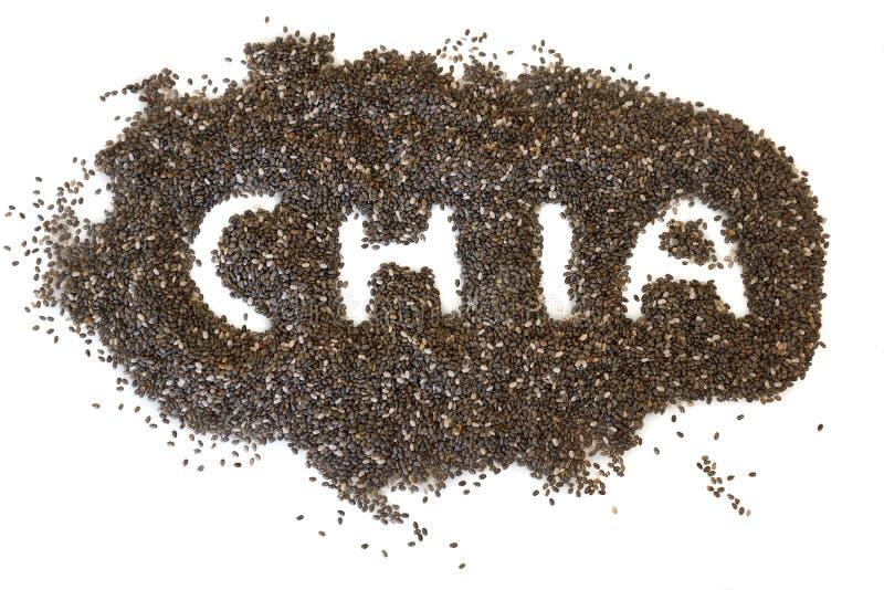 Une pile des graines de chia dispersées sur un fond blanc, avec le chia de mot a défini images libres de droits