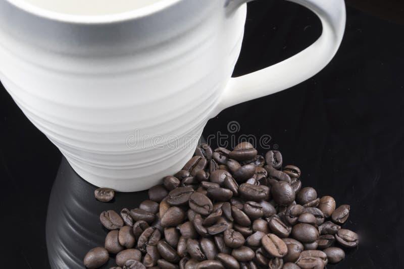 Une pile des grains de café frais et d'une tasse photographie stock libre de droits
