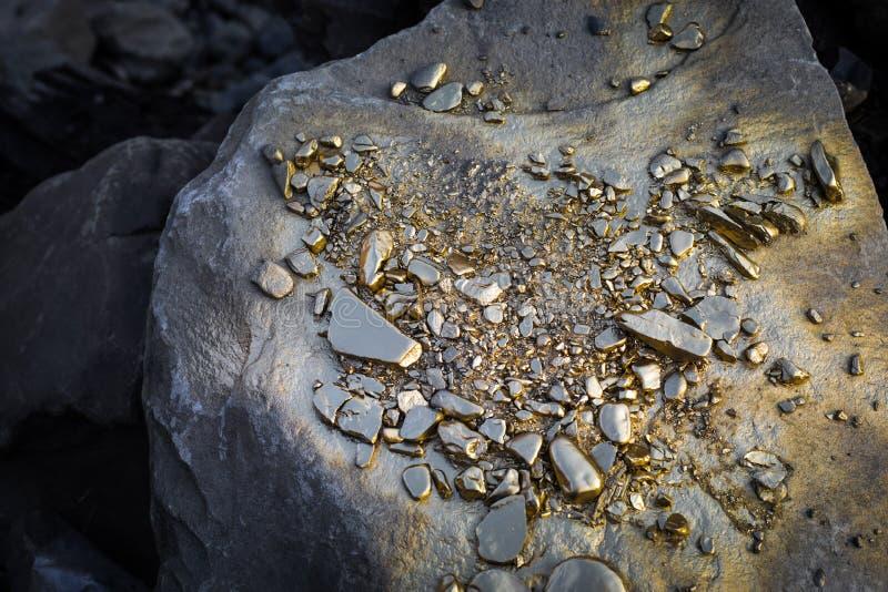 Une pile des grains de pépite d'or, sur la grande pierre de rivière Texture d'or photos stock