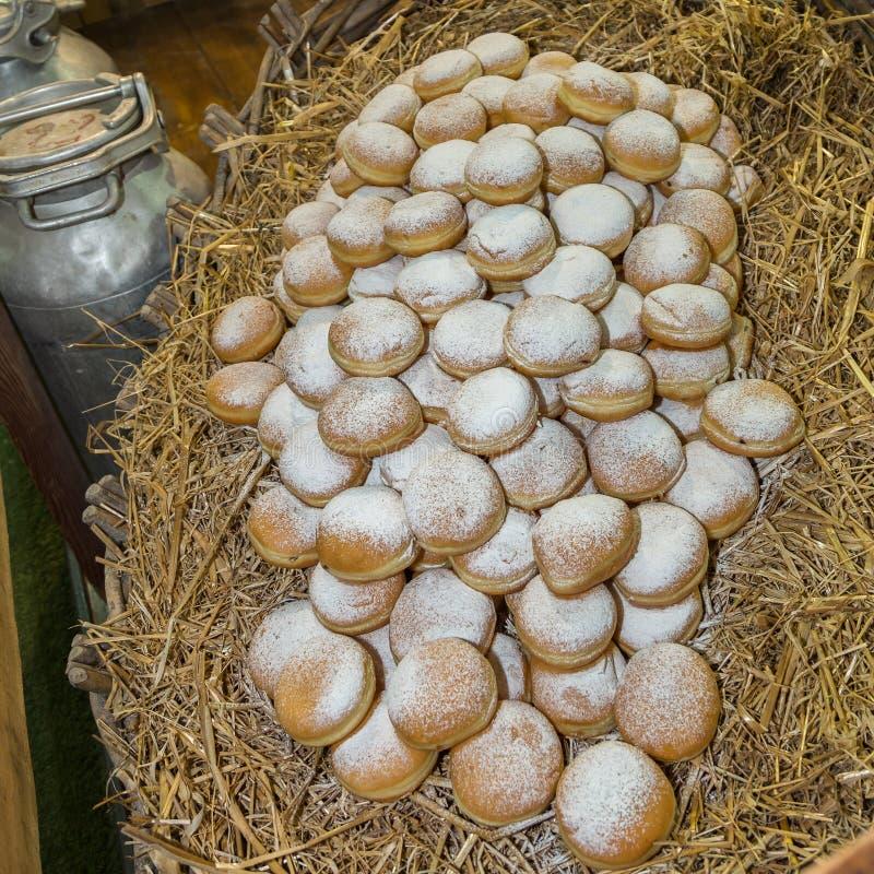 Une pile des pâtisseries remplies du chocolat et de crème sur un lit de paille photos stock