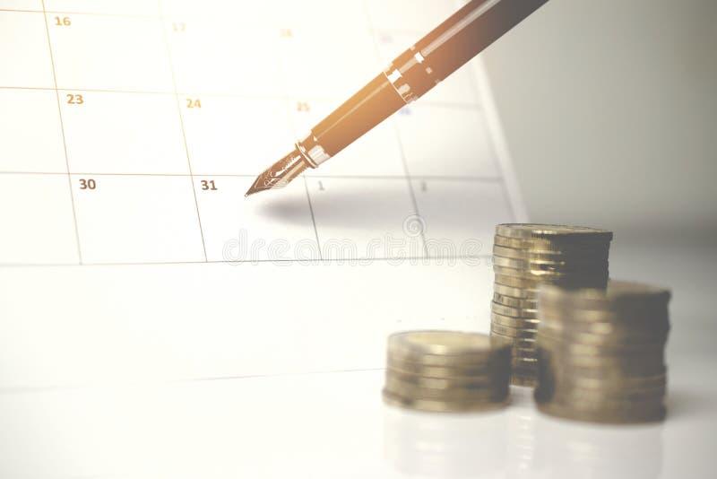 Une pile des pièces de monnaie et un stylo sur le calendrier image libre de droits