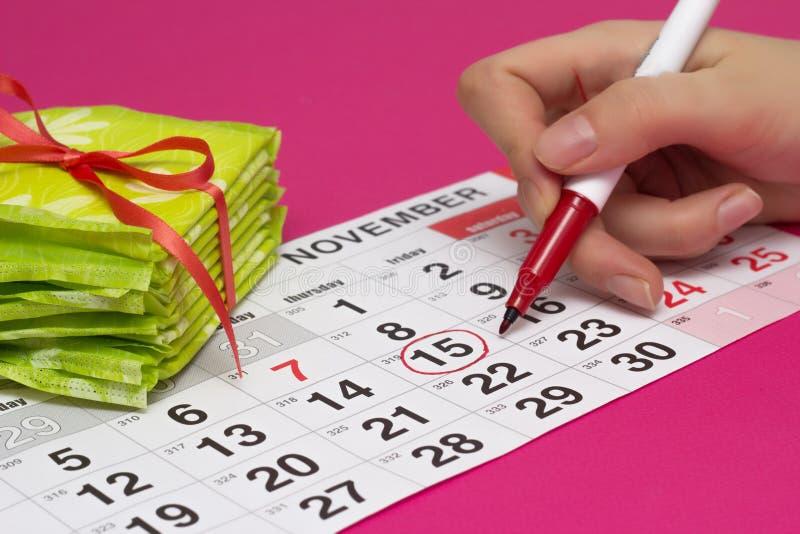 Une pile des protections et d'une fille entoure les jours sur le calendrier avec un stylo feutre rouge quand elle a ses règles, p image libre de droits