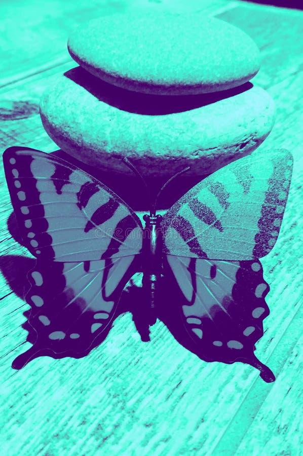 Une pile et un papillon en pierre équilibrés dans Teal photos stock