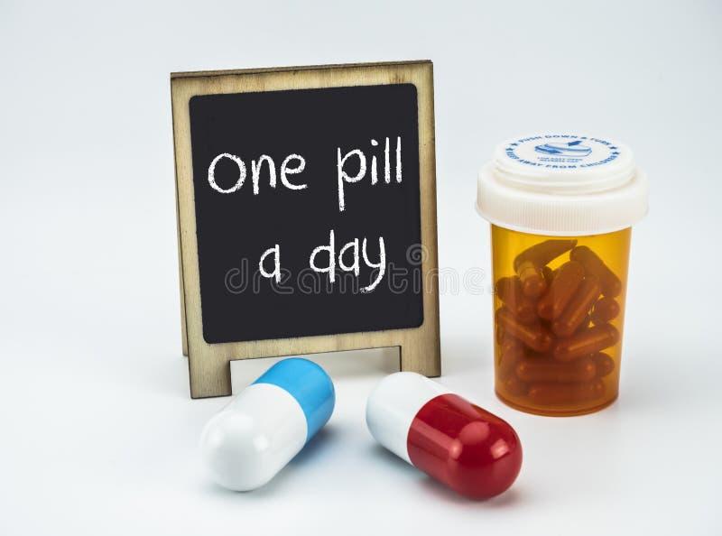 Une pilule par jour sur un tableau blanc à côté des bouteilles de médecines image libre de droits
