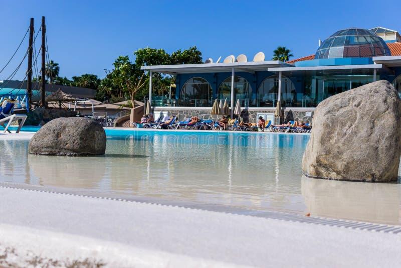 Une piscine d'hôtel avec les baigneurs de touristes du soleil avec deux pierres dans l'eau e images libres de droits