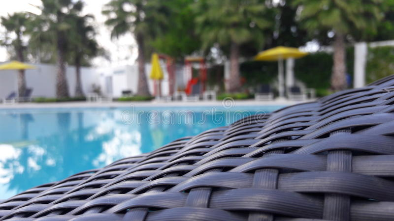 Une piscine trouble sur le fond d'une chaise de piscine photo stock