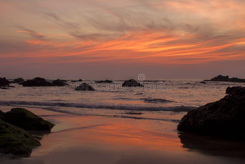 Une plage sablonneuse sur le fond des roches dans la mer et le ciel pourpre rose orange lumineux de coucher du soleil images libres de droits