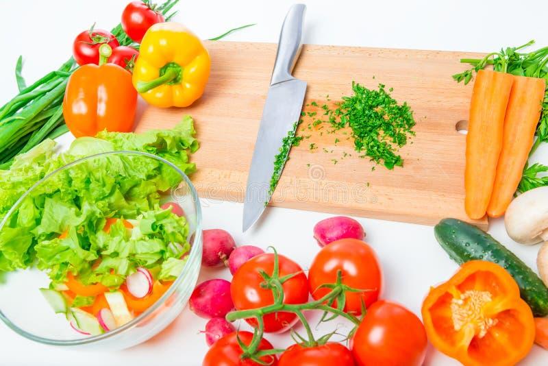 une planche à découper en bois, un couteau et des légumes frais pour la salade photo libre de droits