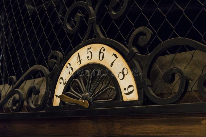 Une plaquette antique avec des chiffres et un indicateur de fer utilisé dans l'ascenseur image libre de droits