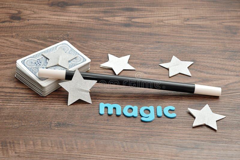 Une plate-forme des cartes avec une baguette magique de magicien, des étoiles et la magie de mot photographie stock
