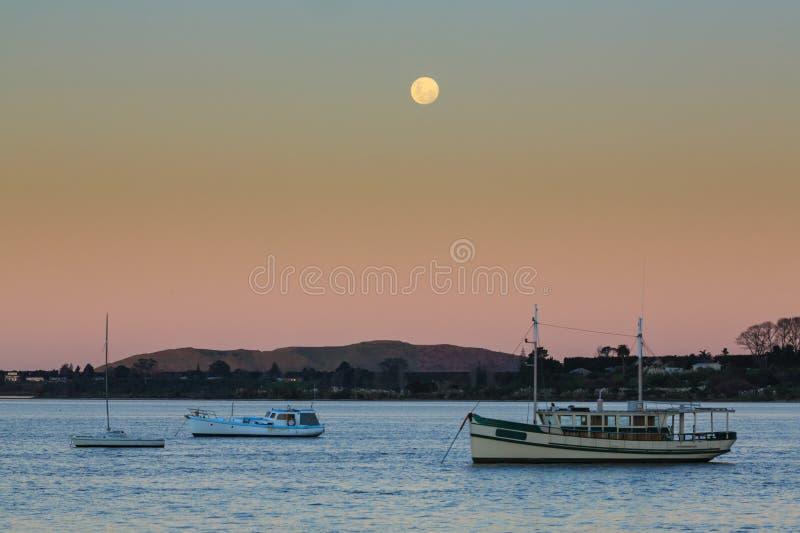 Une pleine lune se levant au-dessus des bateaux dans un port image libre de droits