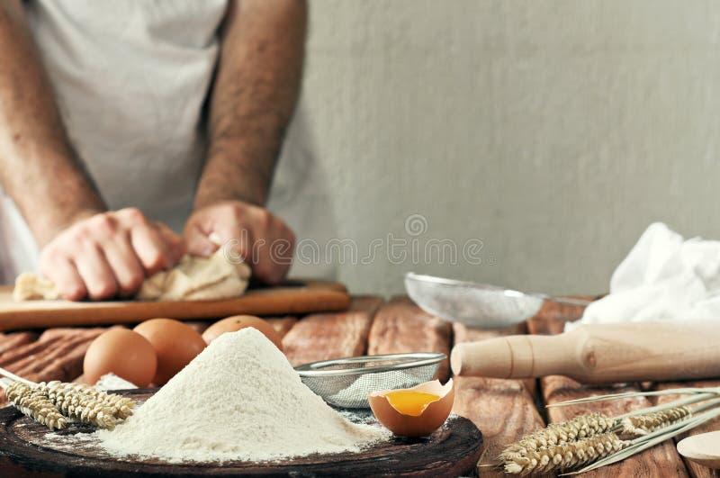 Une poignée de farine avec l'oeuf sur une cuisine rustique image libre de droits